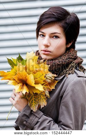 Beautiful brunette romantic woman with short hair holding bouquet of yellow autumn leaves