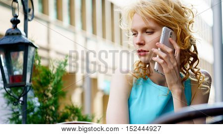 Cute woman with blond curly hair in blue dress sitting in cafe and talking on phone