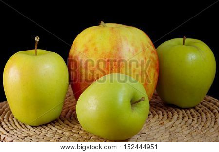 Three green apples and one big apples on the table