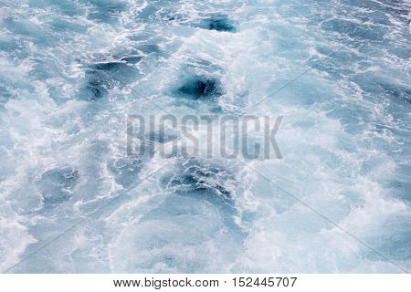 Blue sea and foam water ship tail background. Ripped water with waves from motor boat