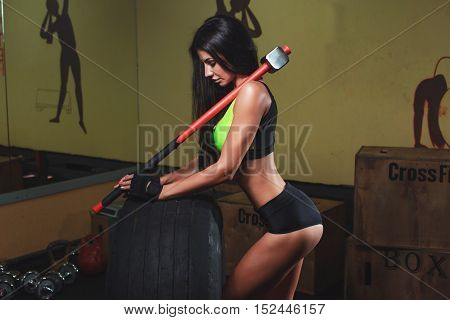 Muscular Young Woman Flipping Tire At Gym. Fit Female Athlete Performing A Tire Flip At Crossfit Gym