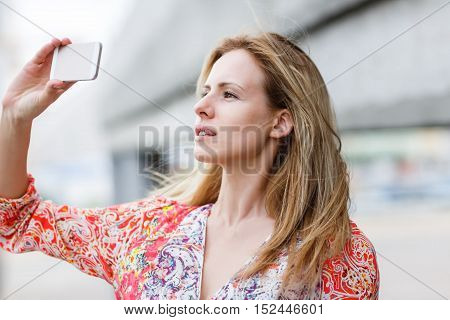 Young cute woman takes photos with her cellphone outdoor