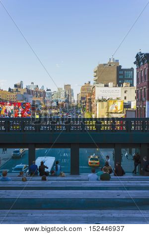 NEW YORK CITY, USA - MAY 6, 2014: The view on 10th Avenue and Midtown from the Highline at May 6, 2014. People are watching the sunset on the wooden stairs in the heart of the