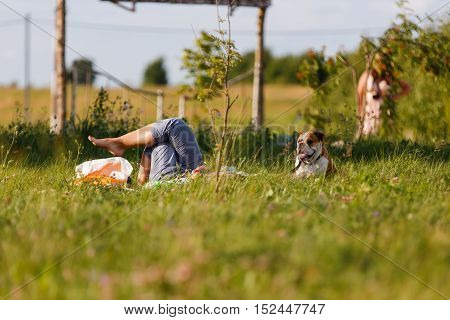 Barefooted woman relaxing lying in a meadow with a dog