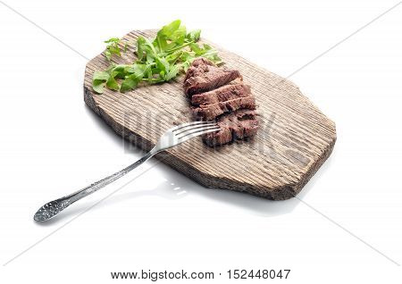 Beef with fork on wood board. Isolated on white. Path included