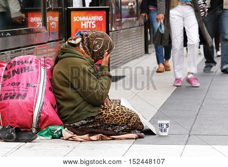 Stockholm, Sweden - June 24, 2014: An unknown woman sits quietly and asking for money with a mug in front of her on Drottninggatan.