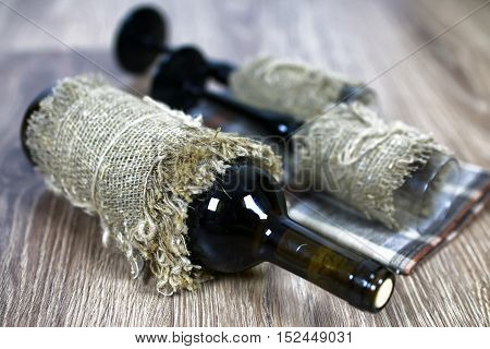 Decorated bottle of fine wine on a wooden table with glass