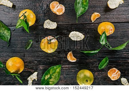 Top view of mandarins with green leaves over dark wooden surface