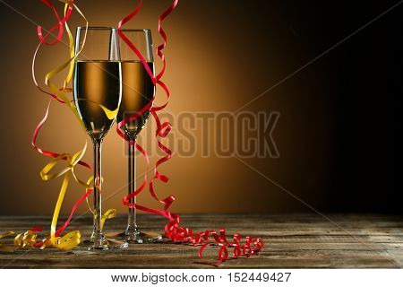 Two glasses of champagne decorated with gold and red streamer