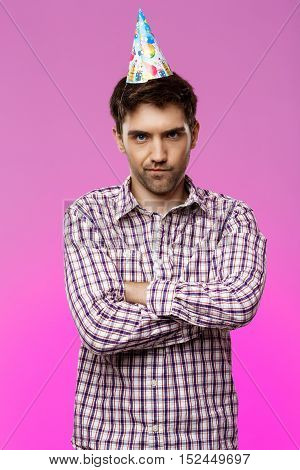 Resentful young handsome man posing with crossed arms over purple background. Birthday party. Copy space.