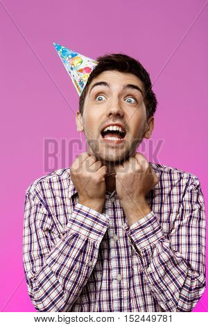 Handsome man trying to take off birthday hat over purple background. Copy space.