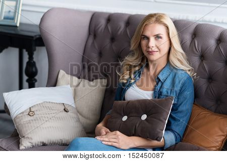 Feeling cozy. Portrait of young pretty blond-haired woman sitting on grey vintage couch and holding pillow.