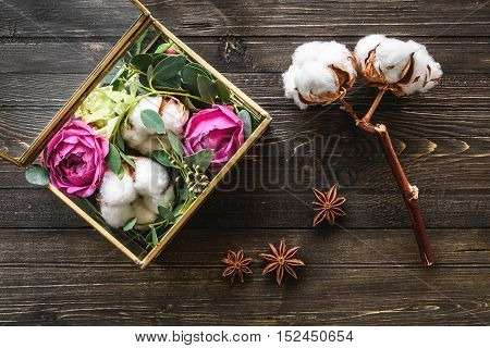 beautiful flowers on darken wooden background cotton and anise