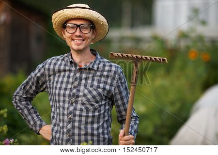 Portrait of smiling gardener young man in hat and glasses holding rake outdoors