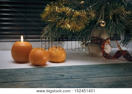 Fur tree branch with christmas decorations next to burning candle and tangerines on window sill horizontal view