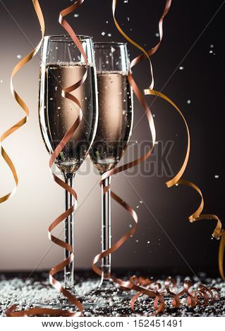 Two glasses of champagne with beautiful festive ribbons and snowflakes
