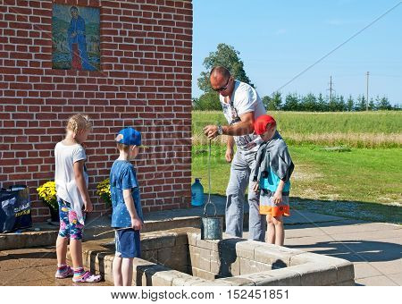 KUREMAE, IDA-VIRUMAA COUNTY, ESTONIA - AUGUST 21, 2016: Man with children take water from The Holy Spring on the place of Marian apparition. Located not far from Puhtitsa Orthodox Dormition Convent