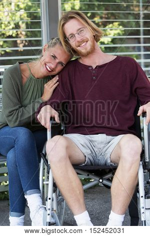 woman hugging young man sitting in wheelchair and smiling