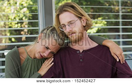 portrait of man and woman hugging and looking sad