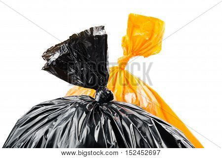 Orange and black garbage bags on white background