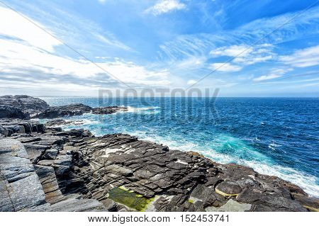 Cloudy blue sky above a blue surface of the North sea and old stones