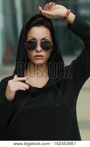 Fashion cool girl in sunglasses in urban background, fashion look. Fashion pretty  woman in rock black style