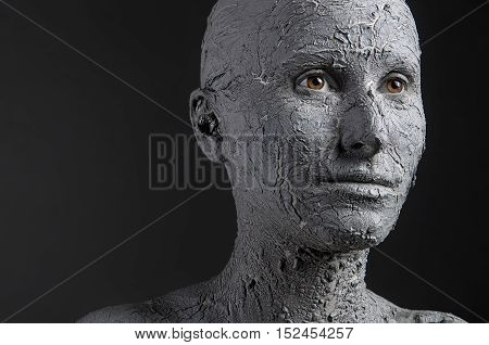 Woman covered in clay. Spa treatment or Halloween mask?