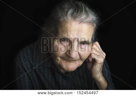 Portrait of a sad elderly woman. Dreaming the past. Selective focus.