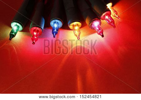 Closeup of Christmas lights glowing on red background