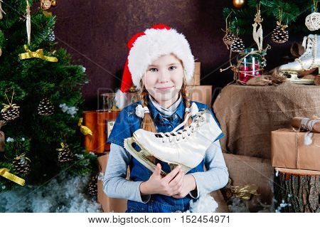 Child in santa hat holding figure skates. Christmas tree and gifts background