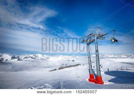 KITZBUEHEL AUSTRIA February 17 2016 - Skiers on ski lift enjoying the view to foggy Alps in Austria and beautiful snowy country panorama in famous Kitzbuehel mountain ski resort