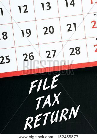Calendar on a blackboard with the words File Tax Return as a reminder to submit your personal or business tax details on time