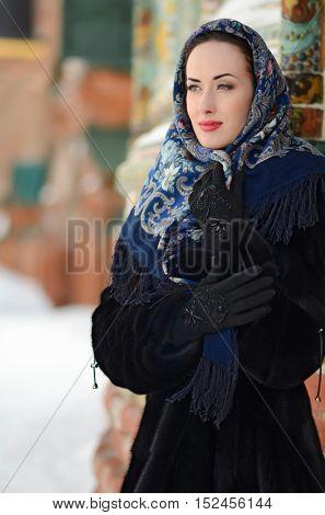 Portrait of beautiful  brunette girl in a blue scarf in the winter