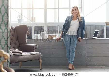 At home. Portrait of happy smiling blond woman standing at big panoramic window barefoot at well-furnished home.