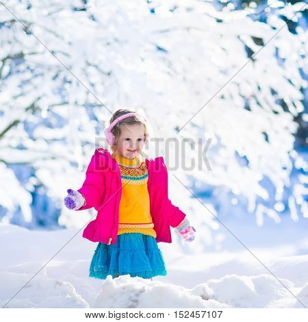 Funny little toddler girl in a colorful knitted hat and warm coat playing with snow. Kids play outdoors in winter. Children having fun at Christmas time. Child enjoying sunny day during Xmas vacation.