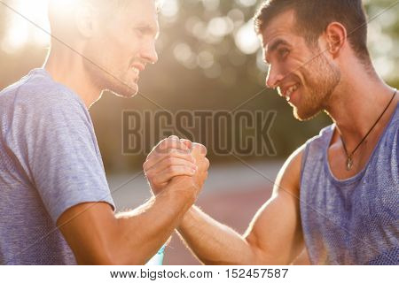 Two hot athletic men shake each others hands on summer day