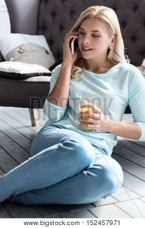 Talking to bestie. Cheerful blond woman sitting on floor with juice glass in front of grey couch and talking per mobile phone.