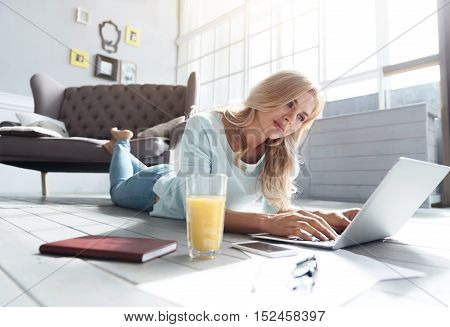 Involved in using. Pretty blond-haired woman lying on floor against grey vintage couch and surfing in new laptop.
