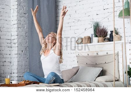 Happy moment. Beautiful blond-haired woman is stretching on her bed before having breakfast in morning,