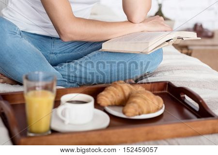 Breakfast will wait. Close up of slim woman sitting on bed and reading book before having breakfast.