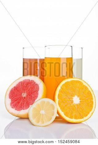 Glasses of healthy grapefruit and orange and lemon juice on white background