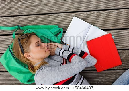 Sleeping student among open workbooks on wooden floor