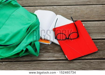 Items for pupil-tablet, notebook, sunglasses, backpack on empty wooden background