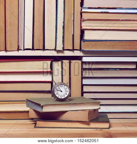 Background from books. Library reading literature. Education back to school. Book shelf bookcase. Alarm clock.
