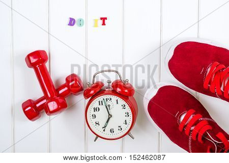 Red sneakers clock and dumbbells on the wooden backgroyund. Do it.