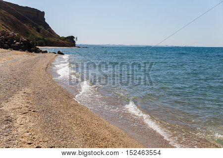 Wild beach with small pebbles and large rock formations. Clean sea soft washes coastline