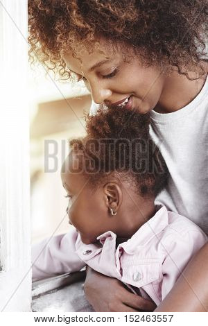 Mother holding baby at the window and smiling