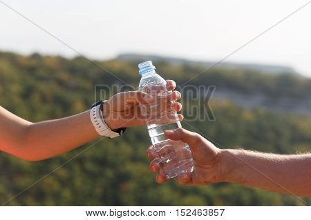 Male and female hand holding plastic water bottle on summer nature background on hot sunny day