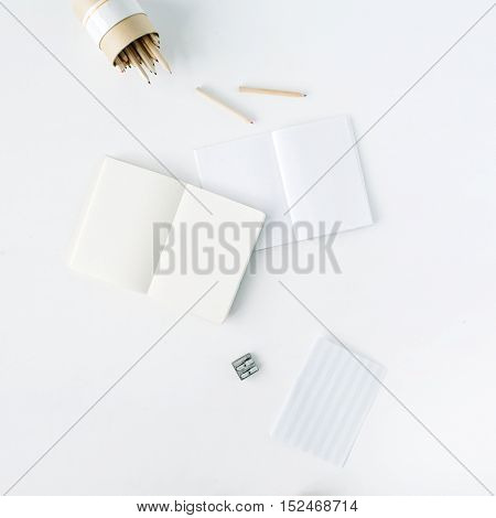 clean blank sketchbook pencils and pencil sharpener on white background. flat lay top view