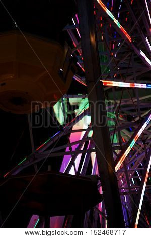 The close-up of lights as well as gondolas of a Ferris wheel at night.